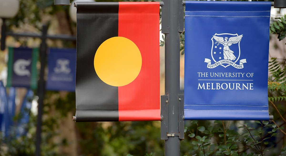 Aboriginal flag and University of Melbourne logo flag side by side