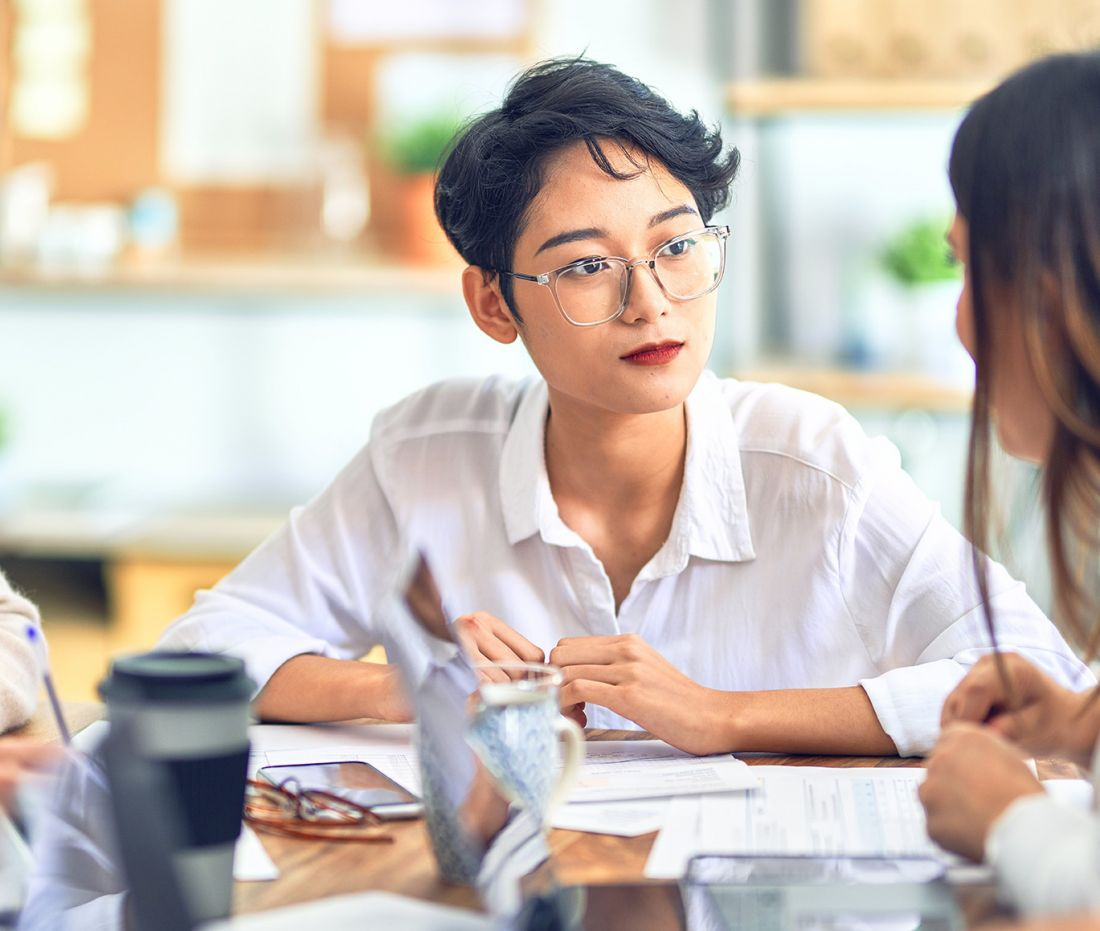 Two young professional talk at a meeting room table.