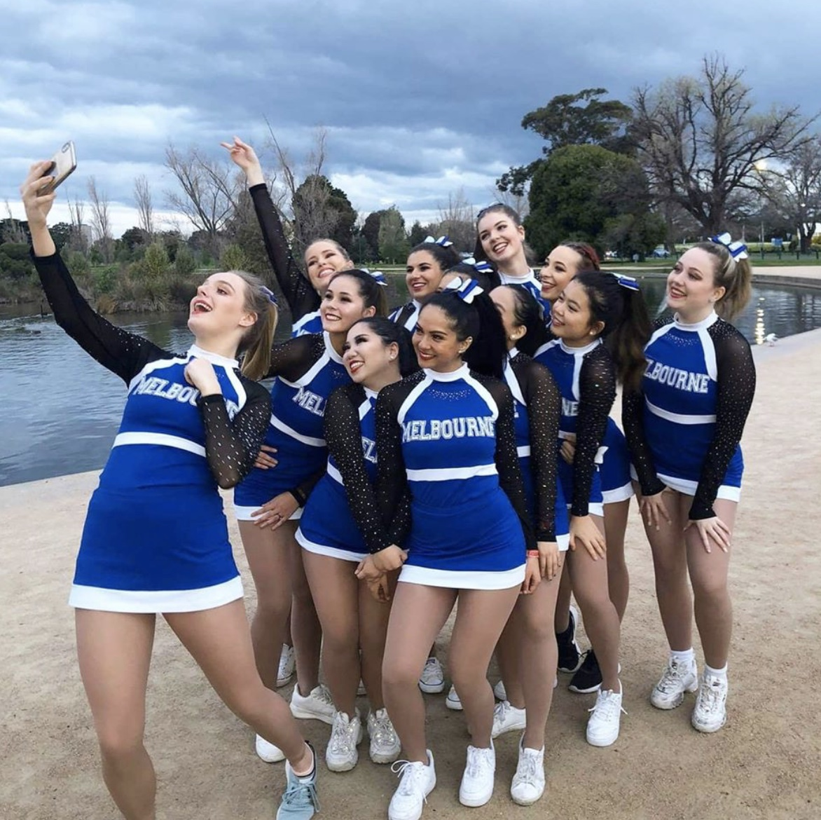 Cheerleading team taking a selfie by a pond