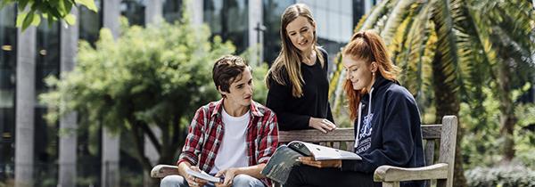 Three students reading a textbook